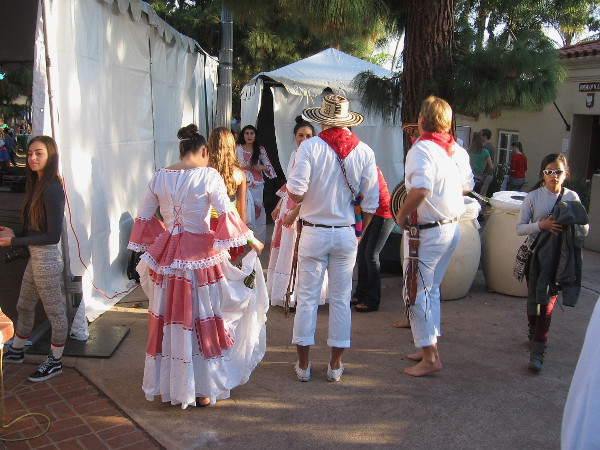 Performers in folk costumes behind the House of Pacific Relations International Cottages stage during December Nights in Balboa Park.