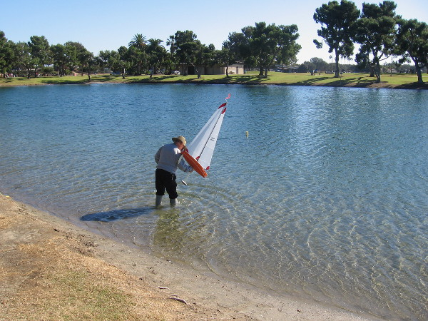 Wading out, in order to place one model sailboat into the water.