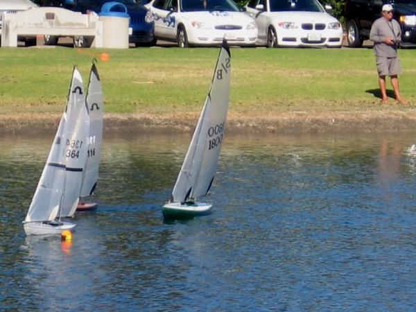 Three model sailboats tack to go around a tiny buoy.