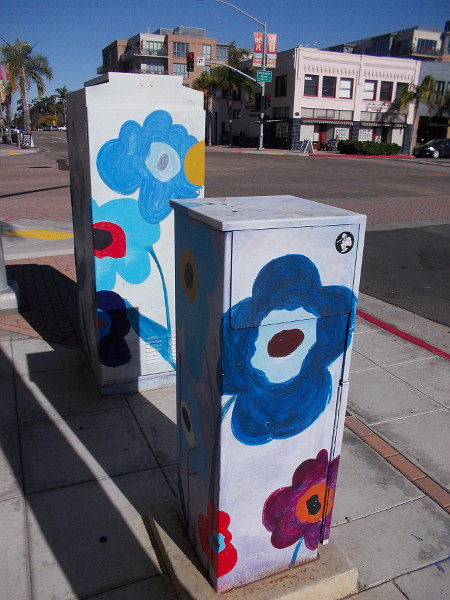 Large painted flowers add color to an otherwise ordinary intersection.