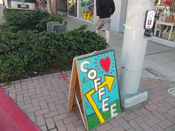 A bold, artistic sign entices people to grab a cup of coffee nearby.