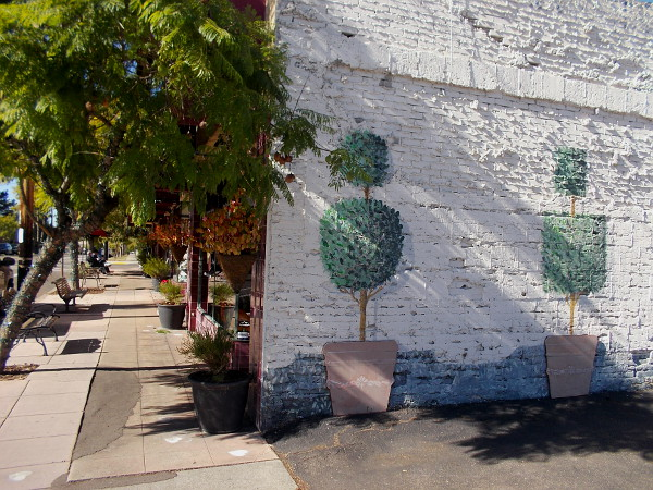 Greenery painted on an old brick wall seems to blend with lush trees along the sidewalk.