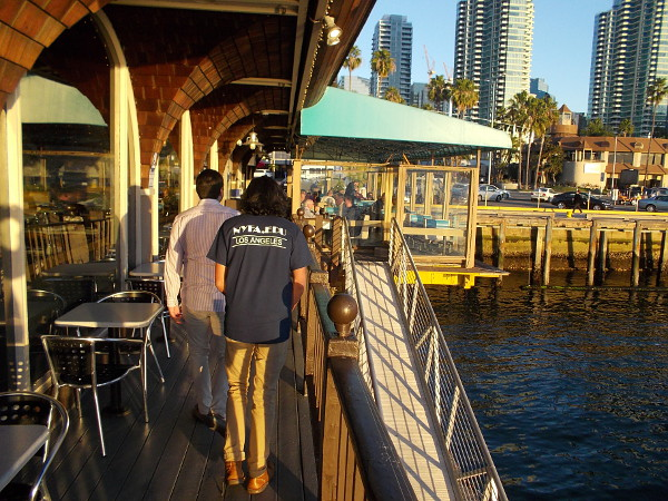 People walk along narrow outdoor deck of Anthony's Fishette, a popular casual dining spot for half a century in downtown San Diego.