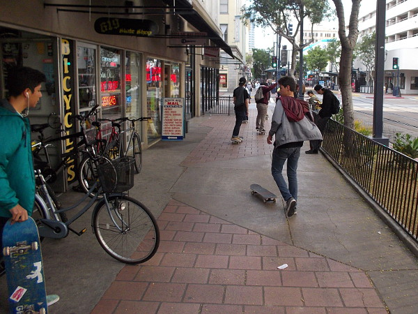 A group of young skateboarders cruises down C Street.