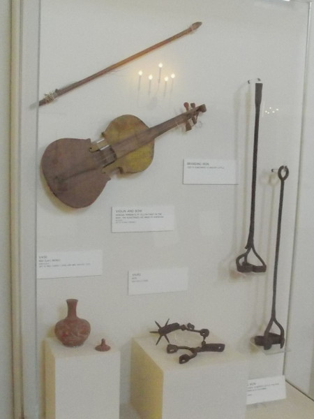 Old violin with bow, a branding iron used by rancheros to identify cattle, and iron spurs are among the many historical objects on display.