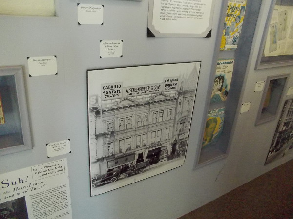 On the wall are many historical photos and artifacts, including an image from around 1930 of a cigar factory on 4th Street in San Diego.