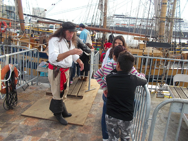 Captain Swordfish makes a scene, distracting those who are boarding the Lady Washington. Nobody notices what that first innocent-looking pirate is up to.