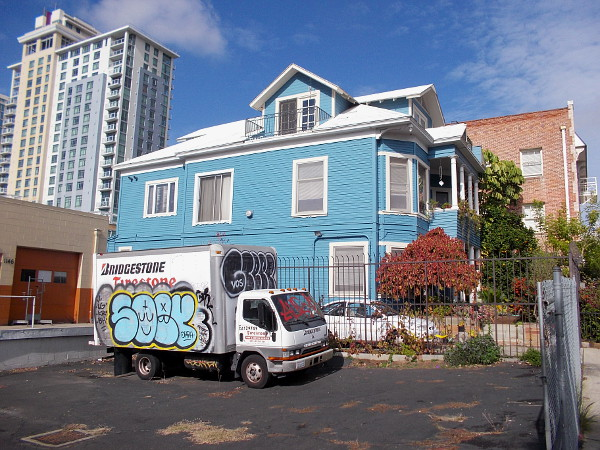 Graffiti on a truck, an old blue house, and a modern high-rise, together in one photo.