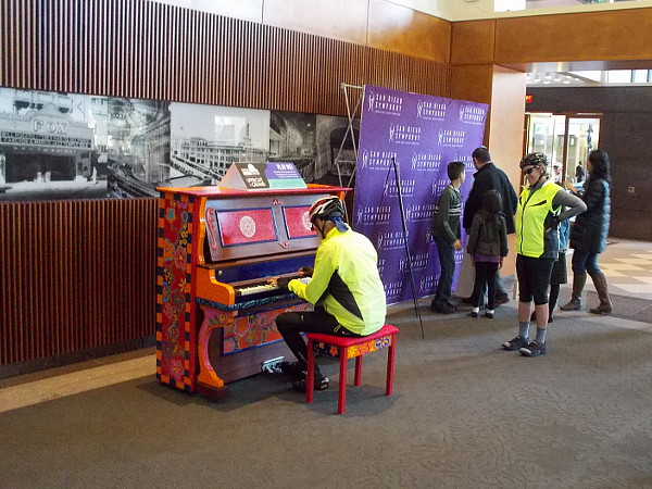 Some bicyclists stopped by to play the public upright piano in the lobby of Symphony Towers near the box office.