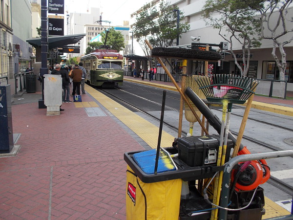 Clean and Safe equipment in the foreground, as a Silver Line vintage trolley approaches the Fifth Avenue station.
