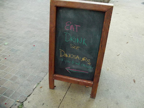 Sign near Downtown Johnny Brown's at Civic Center Plaza reads Eat Drink See Dinosaurs if you drink enough.