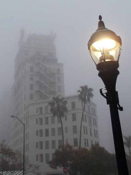 The historic El Cortez Hotel seems to vanish into the gray morning fog.