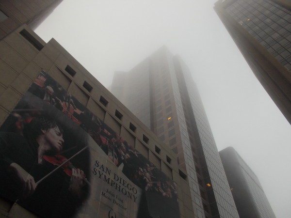 Looking up toward the unusually thick fog past a San Diego Symphony banner downtown.