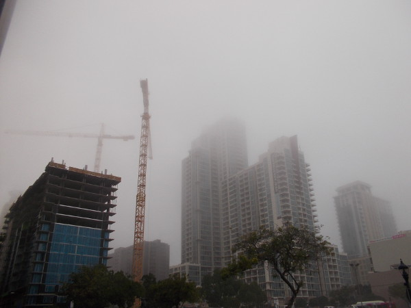 Cranes and construction next to several high towers, in a San Diego fog.