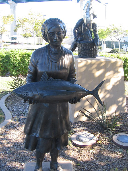 Sculpture of woman fish processor holding a large tuna. This area south of downtown was once the home of many San Diego canneries.