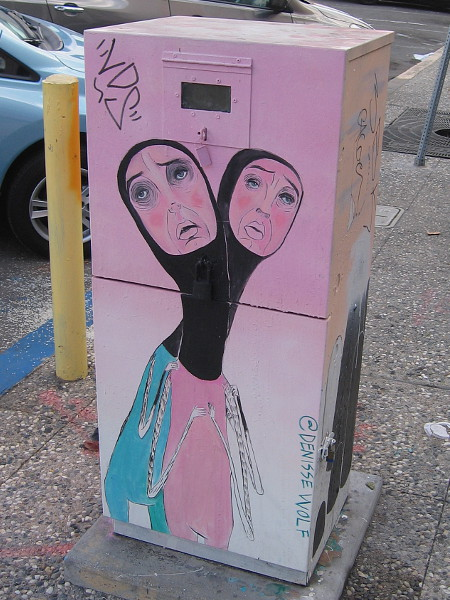 Two faces rise from one neck in this unusual utility box street art.