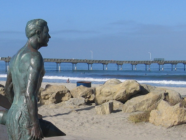 A bronze hero stands guard on the sand in Ocean Beach. The long OB pier stretches out into the Pacific Ocean in the background of this photo.