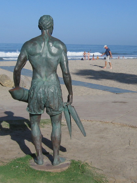 The muscular bronze lifeguard statue holds a rescue tube and a pair of swim fins