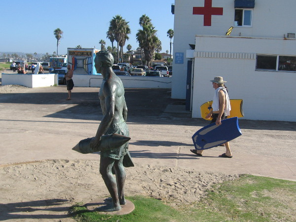 Beachgoer with two boogie boards passes between the bronze sculpture and the main Ocean Beach lifeguard station.