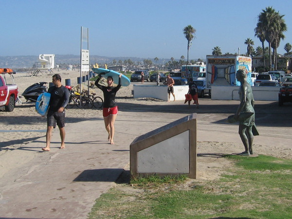A couple of surfer dudes carrying surfboards approach the memorial plaque, a few feet from the lifeguard tribute statue.