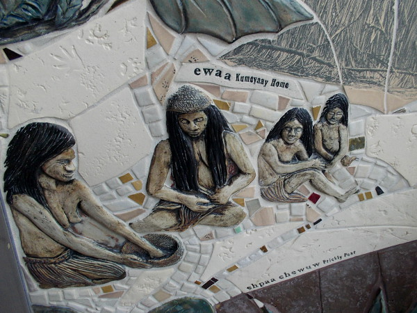 Native American Kumeyaay from the San Diego area work near the foot of an Ewaa, or dome shaped home made of sycamore and oak tree branches.