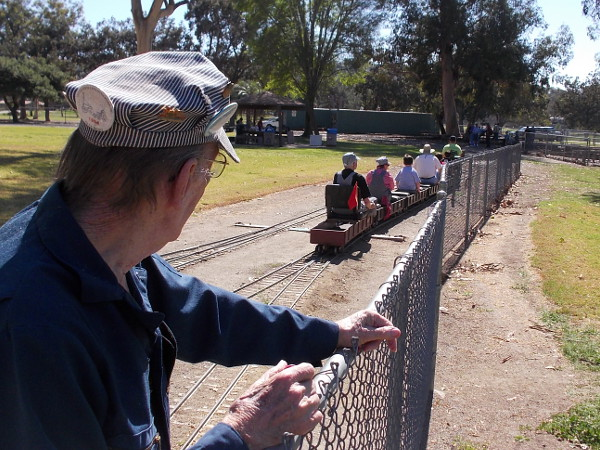 "A ""live steam"" enthusiast watches folks ride a small train through Rohr Park, in San Diego's South Bay."