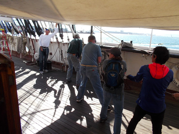 Volunteers at the Maritime Museum of San Diego haul a rope on the deck of Star of India to help raise a protective tarp above the historic ship.