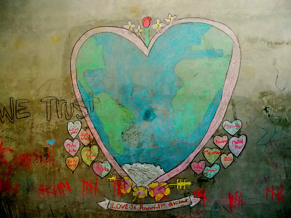 And young people created this chalk drawing on a playground wall. A heart encompasses the Earth and a puppy dog. Love is powerful.