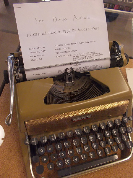 One display case contains an old manual typewriter, and lists from past years of published authors in San Diego.
