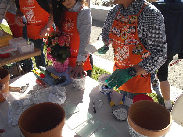 A layer of ceramic tile adhesive is applied to the exterior of clay pots.