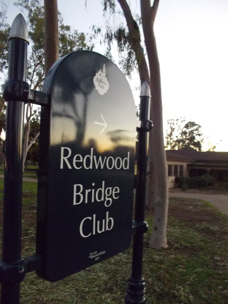 A warm glow and reflection on the Redwood Bridge Club sign at the west edge of Balboa Park.