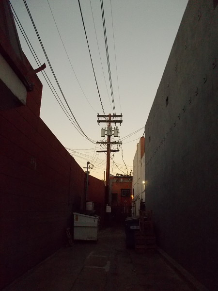 The sky is gradually brightening above a shadowy Hillcrest alley.