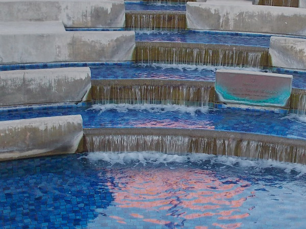A reddish splash in blue water. The fountain in front of Scripps Mercy Hospital.