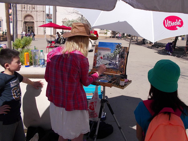 Young people were watching a lady artist paint a scene in Balboa Park.