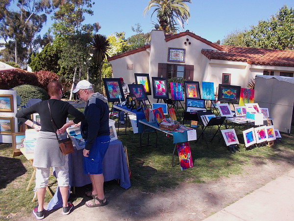 A couple peruses works by local artists out on display in Balboa Park.