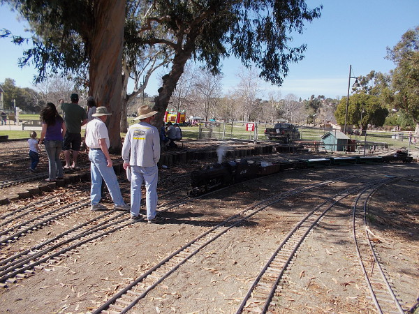 Dedicated train hobbyists have gathered on the surprisingly large rail yard to watch the steam locomotive.
