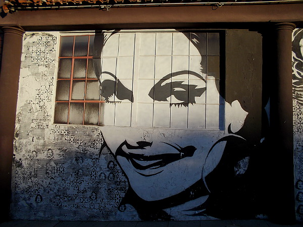 A large smiling senorita mural looks right at you.