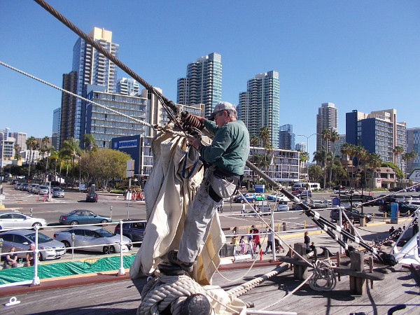Another volunteer works near the bow of the historic tall ship. Downtown San Diego's skyline provides a gleaming backdrop.