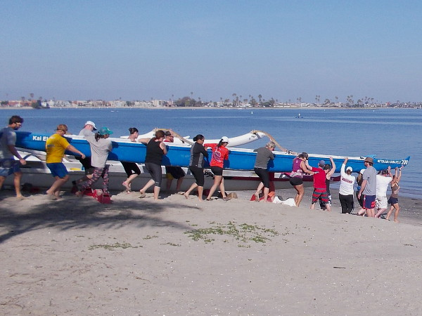 Members and guests of San Diego's Kai Elua Outrigger Canoe Club carry an outrigger canoe across the beach toward the water of Mission Bay.