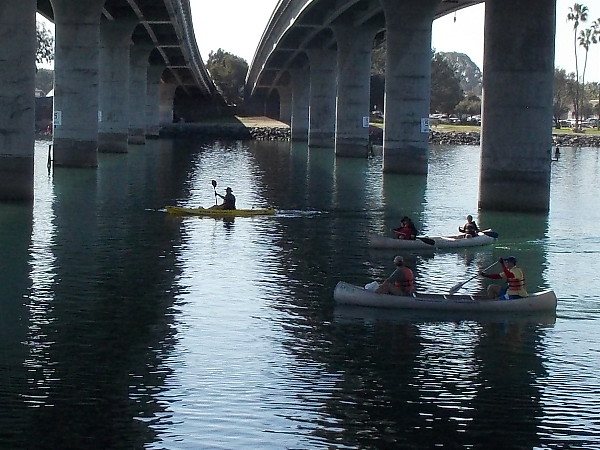 Many canoes and kayaks were passing under the Ingraham Street Bridge between South Cove and Perez Cove, not far from SeaWorld.
