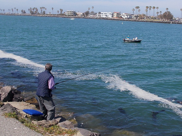 A fisherman on land, and two on the water. Across the Entrance Channel lies Mission Beach.