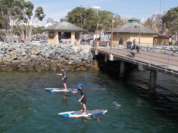 A pair of standup paddleboarders have passed under the Embarcadero Marina Park South Pier, one of my favorite places to visit on San Diego Bay.