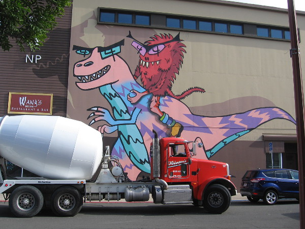 Funny urban art in North Park. A cool T. rex and fuzzy rider rise high above a concrete mixer truck. Created by artist Mark Paul Deren, also known as Madsteez.