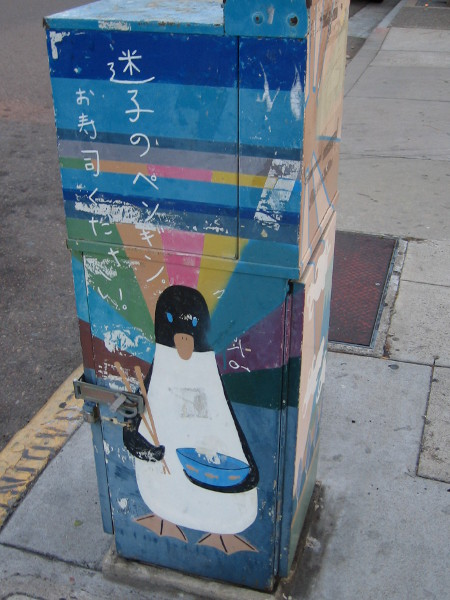 Weathered penguin on utility box has some chopsticks held in a flipper.
