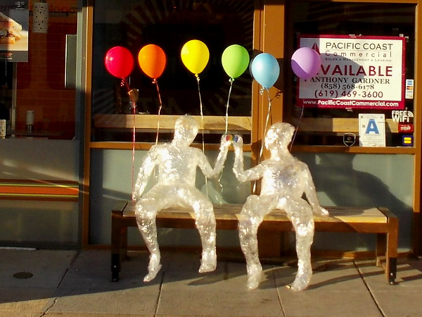 A happy couple made of shining plastic wrap sits on a bench beneath rainbow balloons in Hillcrest. Yes, I did a double take, then got some quick photos!