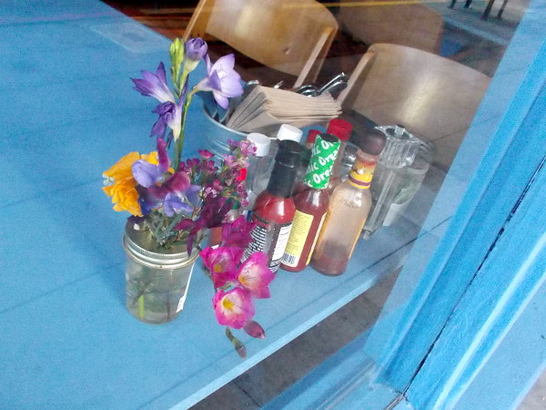 A peek through a window at flowers on a table inside a Little Italy breakfast spot.