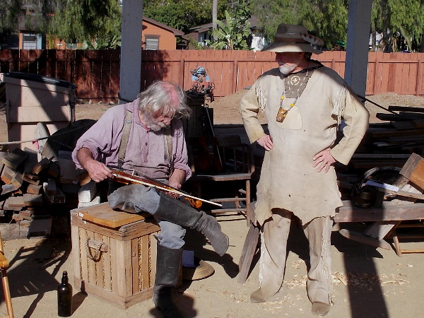 Two rugged mountain men, one with a fiddle, hang out behind Seeley Stable at Old Town San Diego State Historic Park.