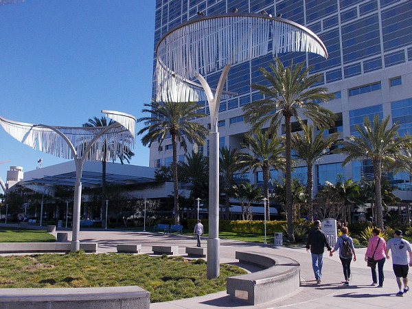 People walk beneath unique tree-like art between the San Diego Convention Center and the Hilton hotel.