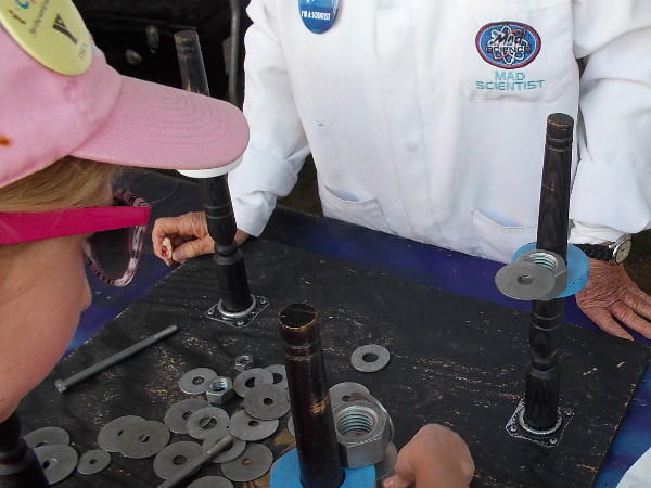 A mad scientist at the San Diego Festival of Science and Engineering shows a kid how to have some fun with magnets!