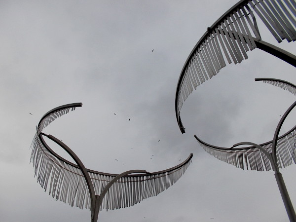 Seagulls circle high above the palm-like kinetic sculptures on a gray, cloudy day.